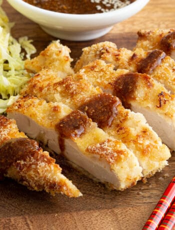 Panko crumbed katsu chicken with chopsticks, cabbage and tonkatsu sauce.
