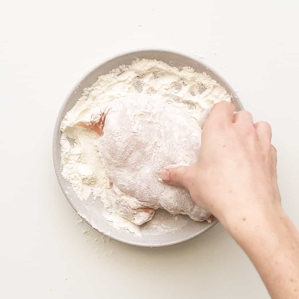 Coating the chicken in the flour mixture.