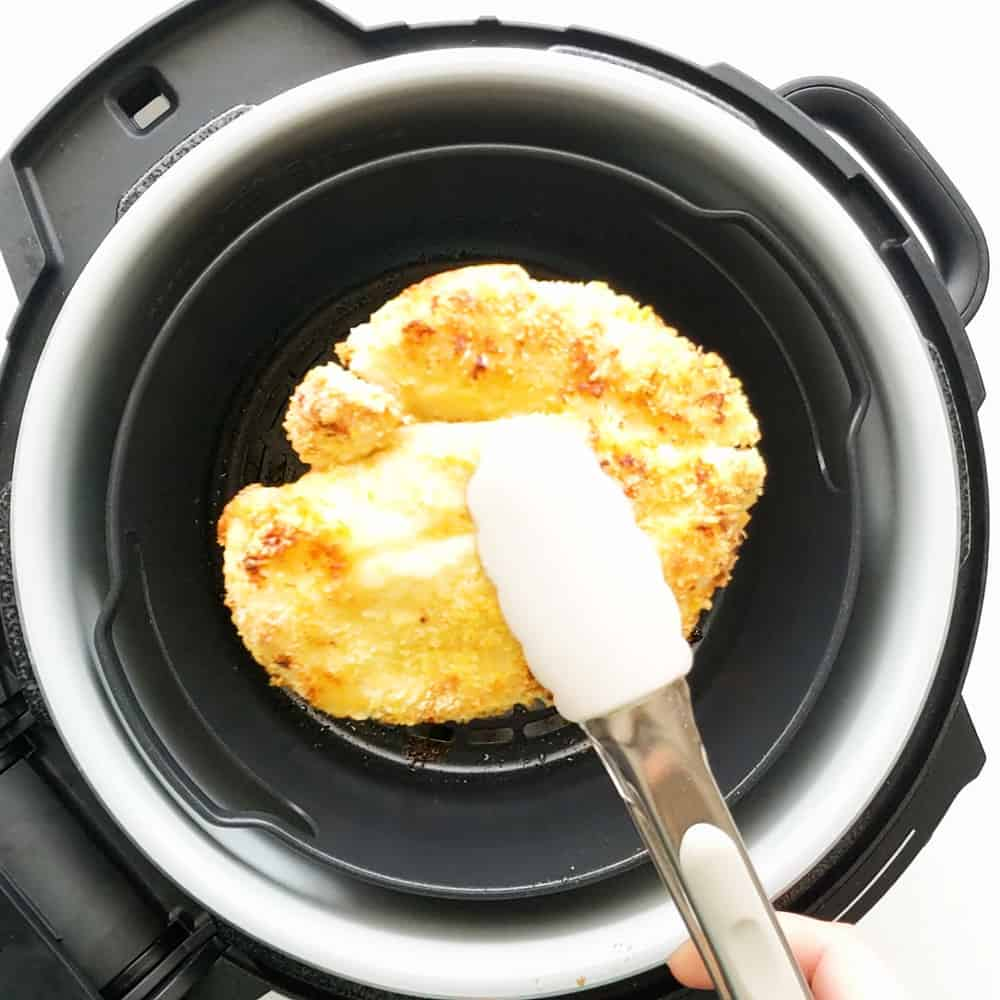 Taking the chicken out of the air fryer.