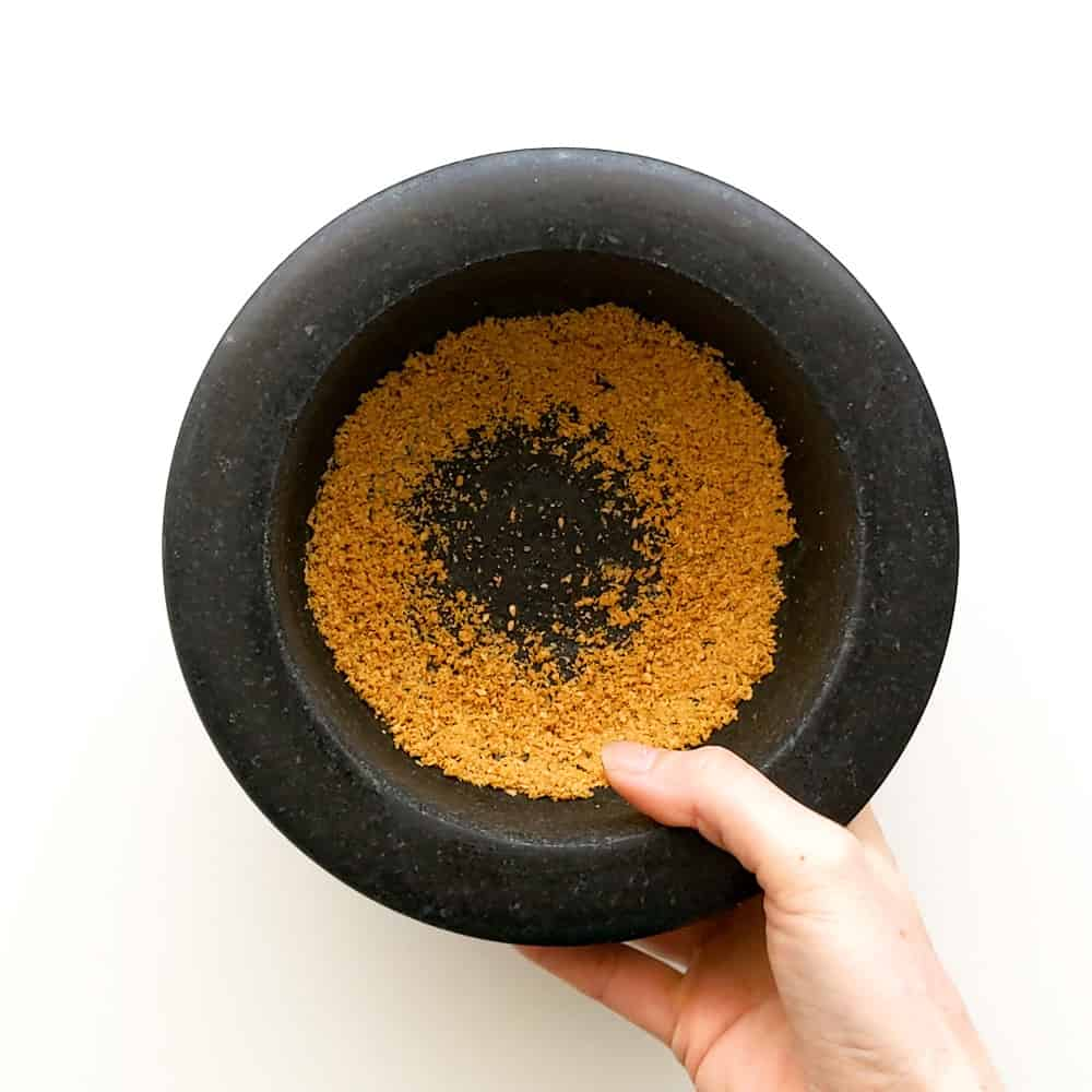 Grinding toasted sesame seeds in a mortar and pestle.