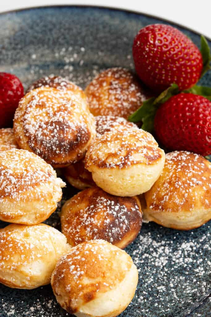 Fresh poffertjes on a blue plate with strawberries.
