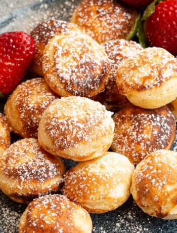 Dutch mini pancakes on a plate with strawberries.