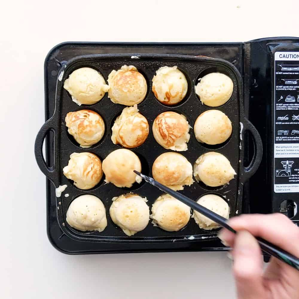 Flipping each poffertjes over with a chopstick.