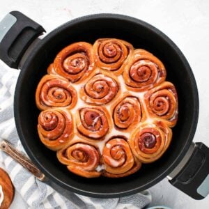 Top down view of freshly baked cinnamon scrolls sitting in a Remoska cooker.