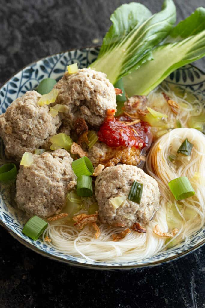 Bakso meatballs in beef broth soup with noodles and bok choy.