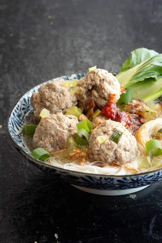 Steaming bowl of bakso soup with noodles and bok choy.
