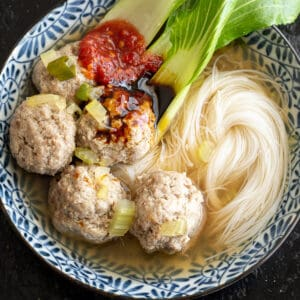 Beef meatballs in a soup broth with noodles and bok choy.