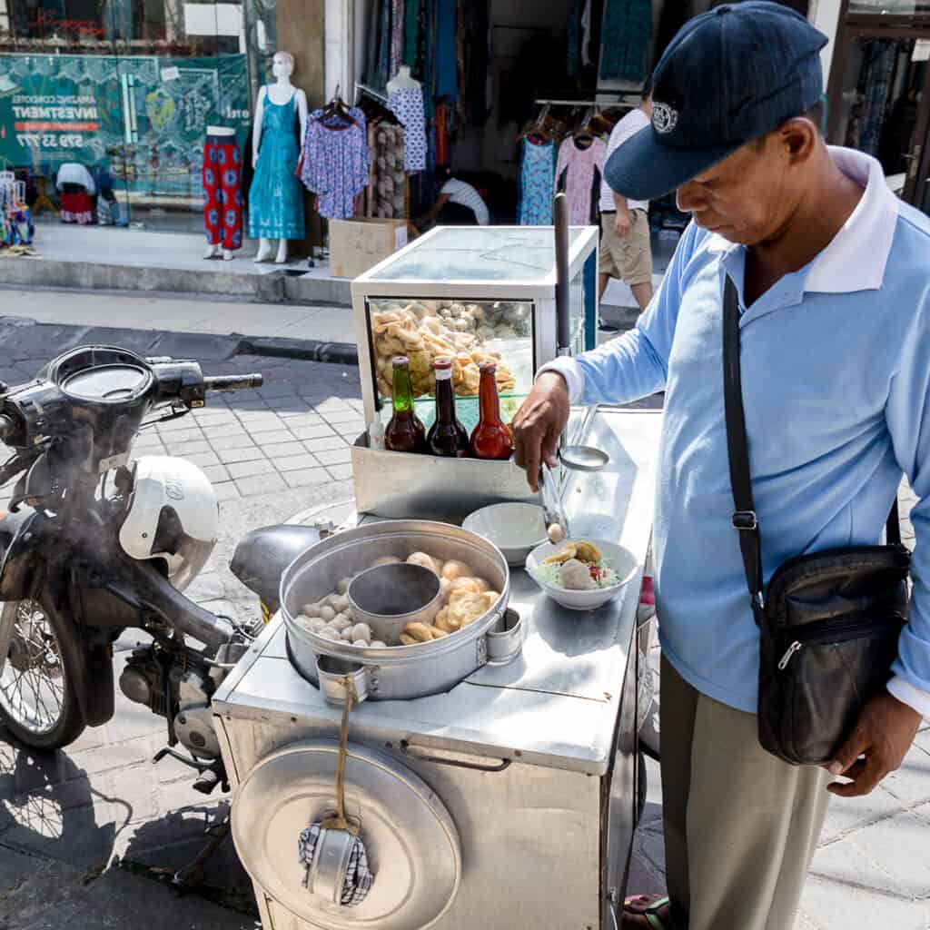 Mr Bakso standing at his street food stall in Bali, Indonesia.