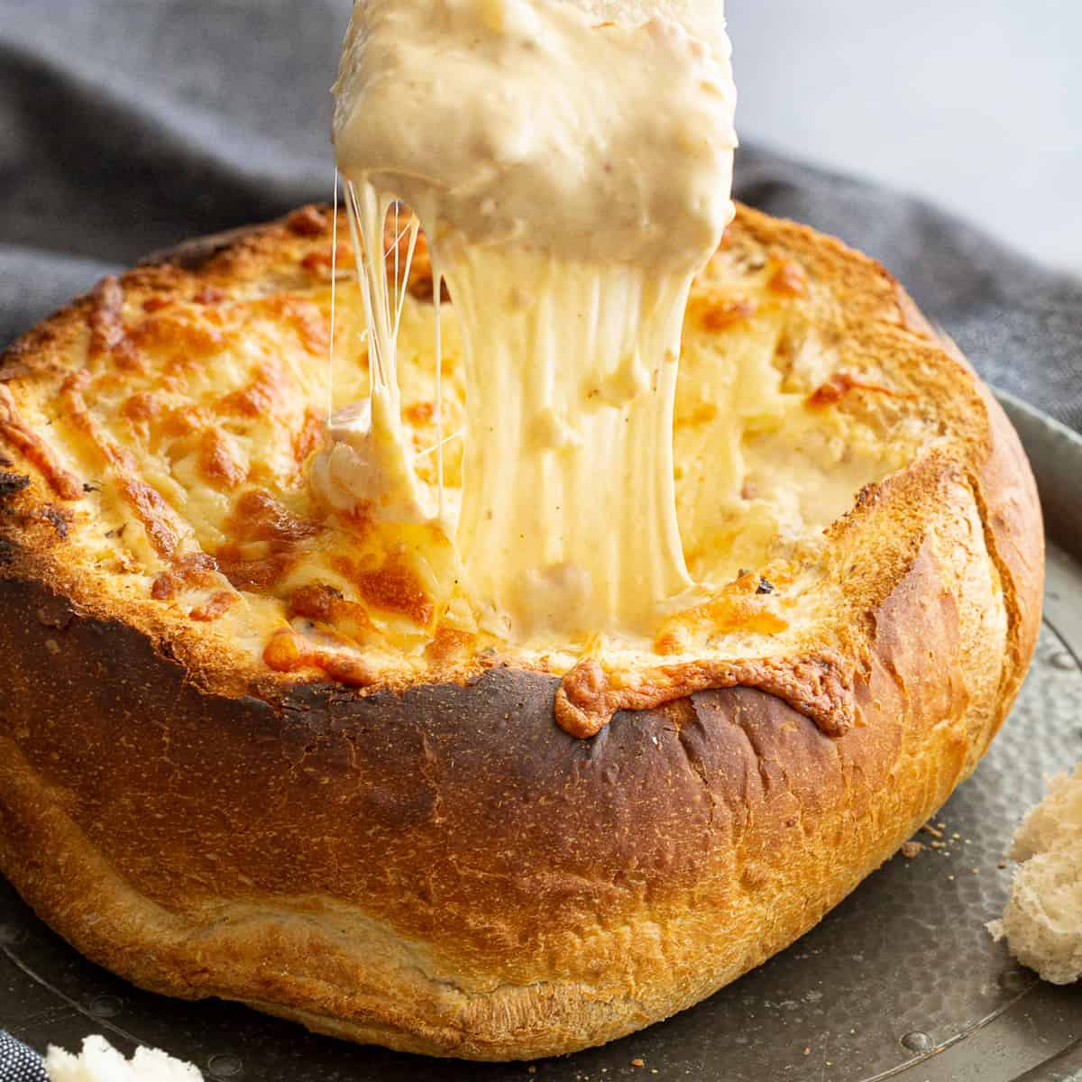 Bread pulling away from melted cheese in a cheese and bacon cob loaf.