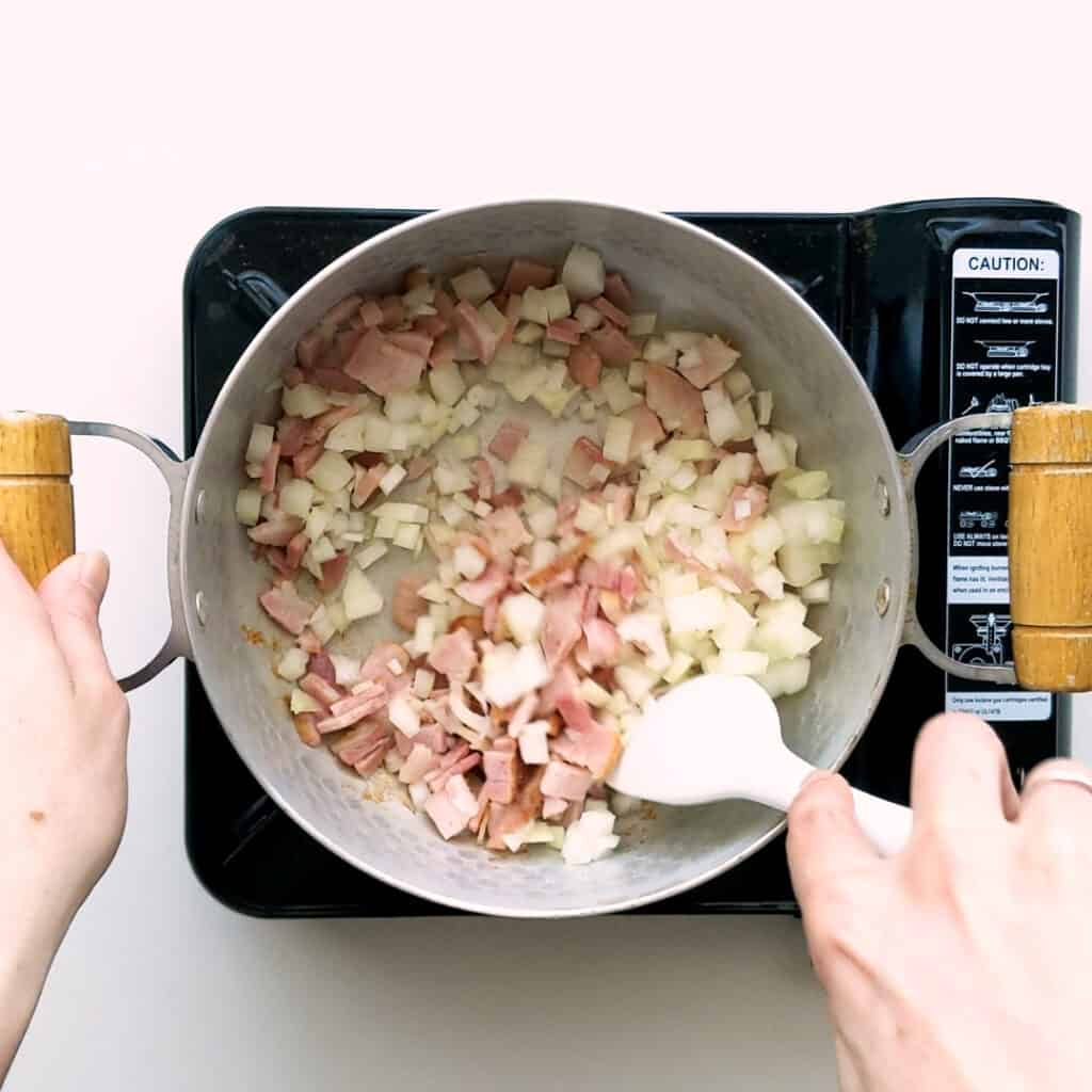 Frying bacon and onion in a saucepan.
