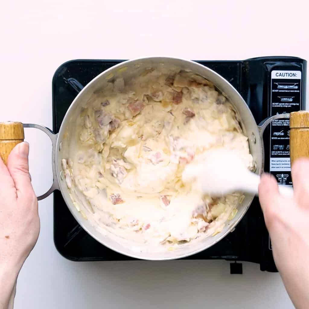 Mixing cream cheese through the bacon and onion mix.