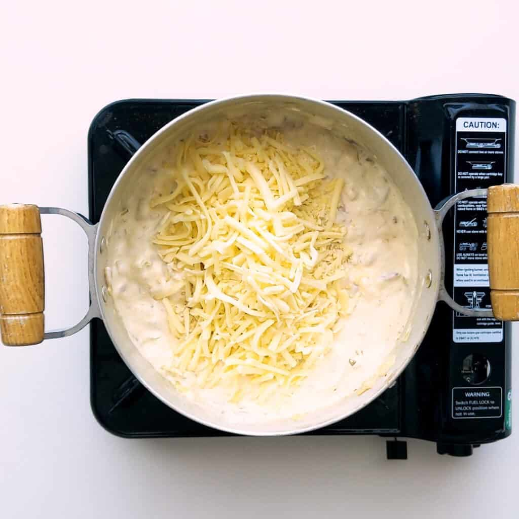 Adding pizza cheese to the saucepan.