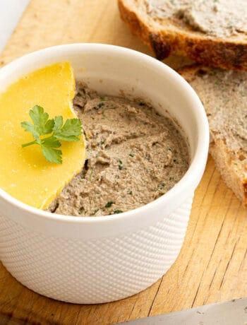 Mushroom pate in ramekin with broken butter seal.