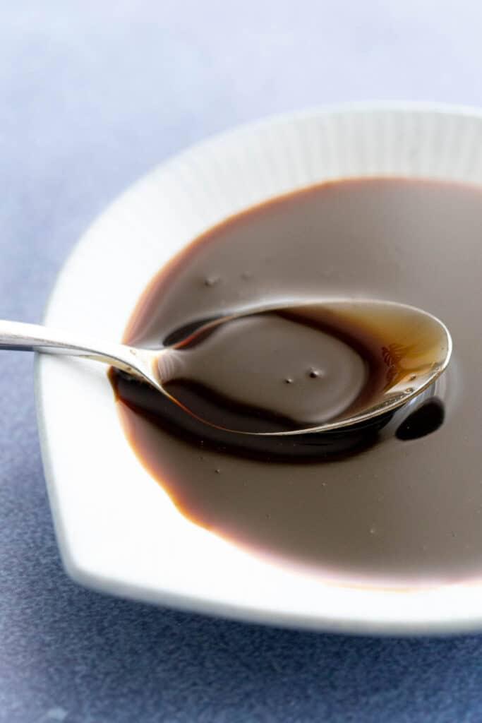 Thick kecap manis on a spoon in a white dish.