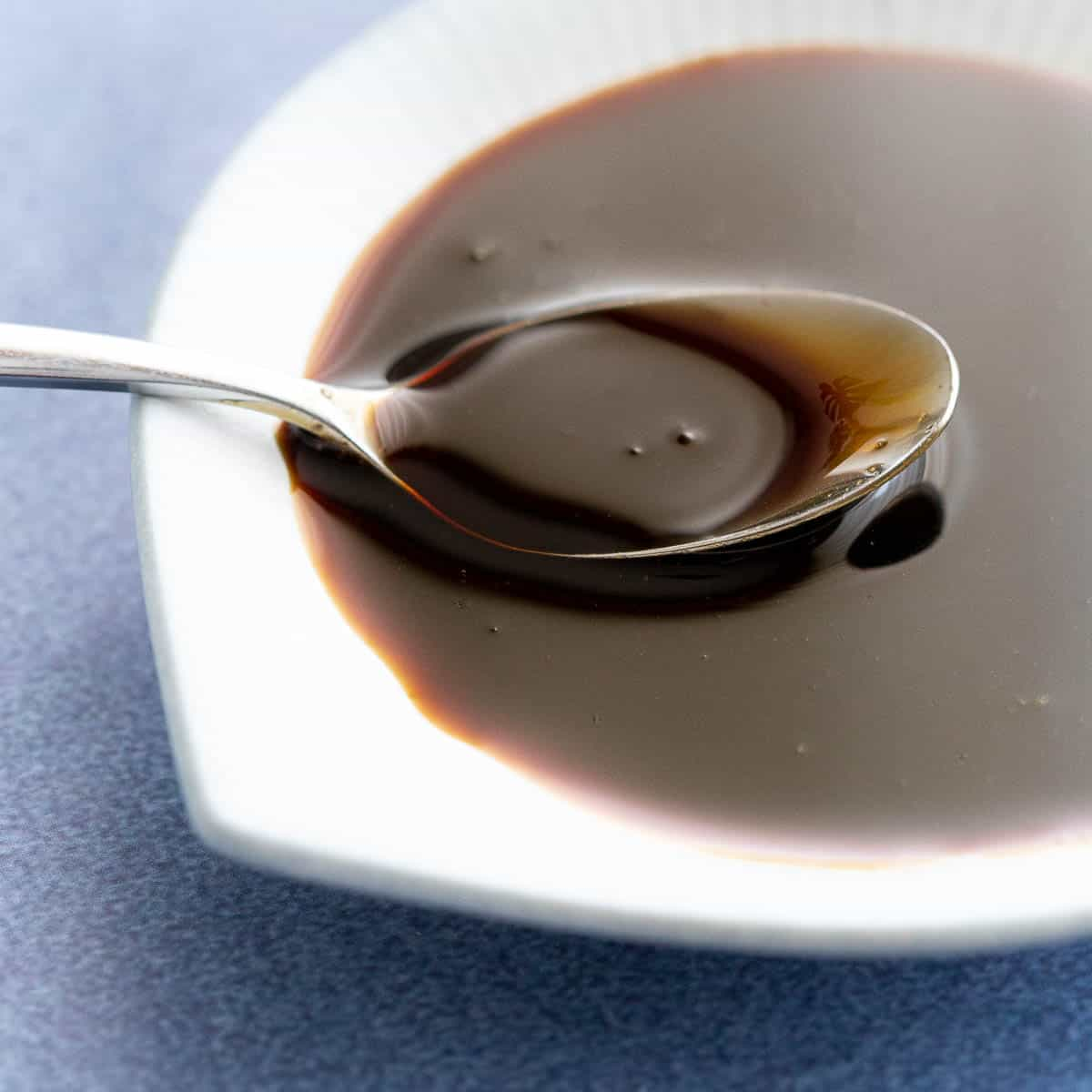 Shiny, thick kecap manis in a small white dish.