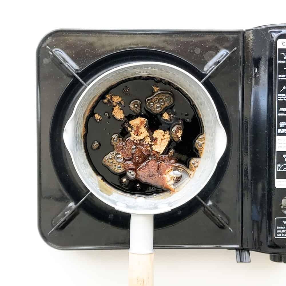Placing brown sugar and soy sauce in small saucepan.