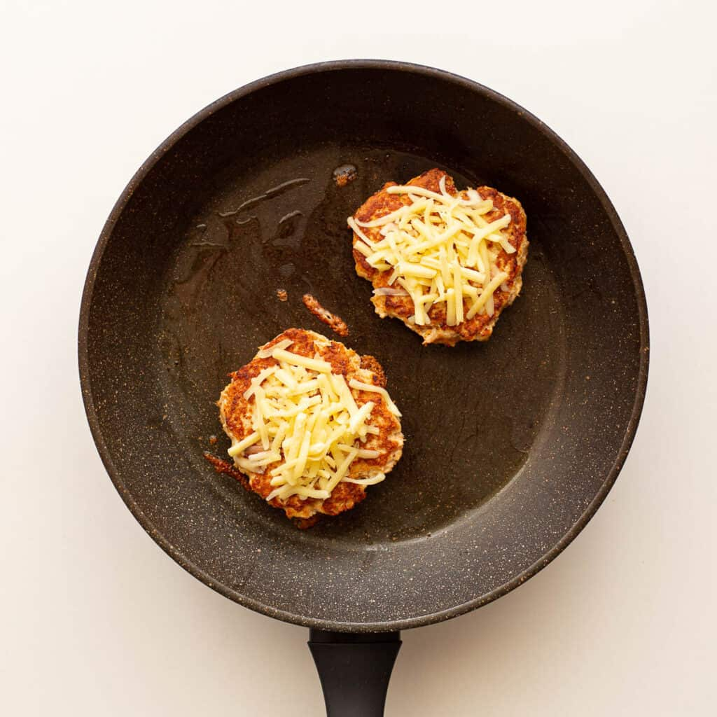 Frying chicken patties with cheese on top.