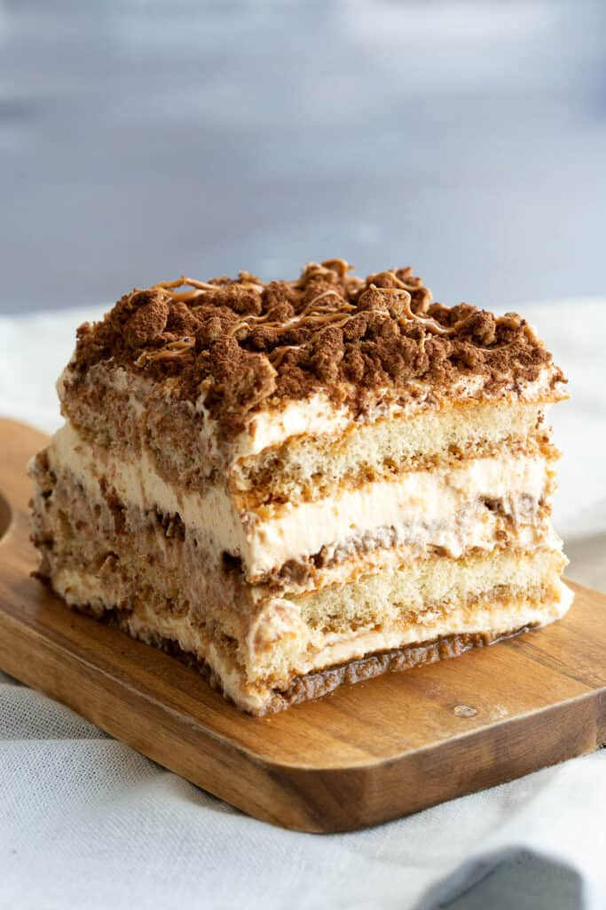 Slice of speculoos tiramisu on a wooden board.