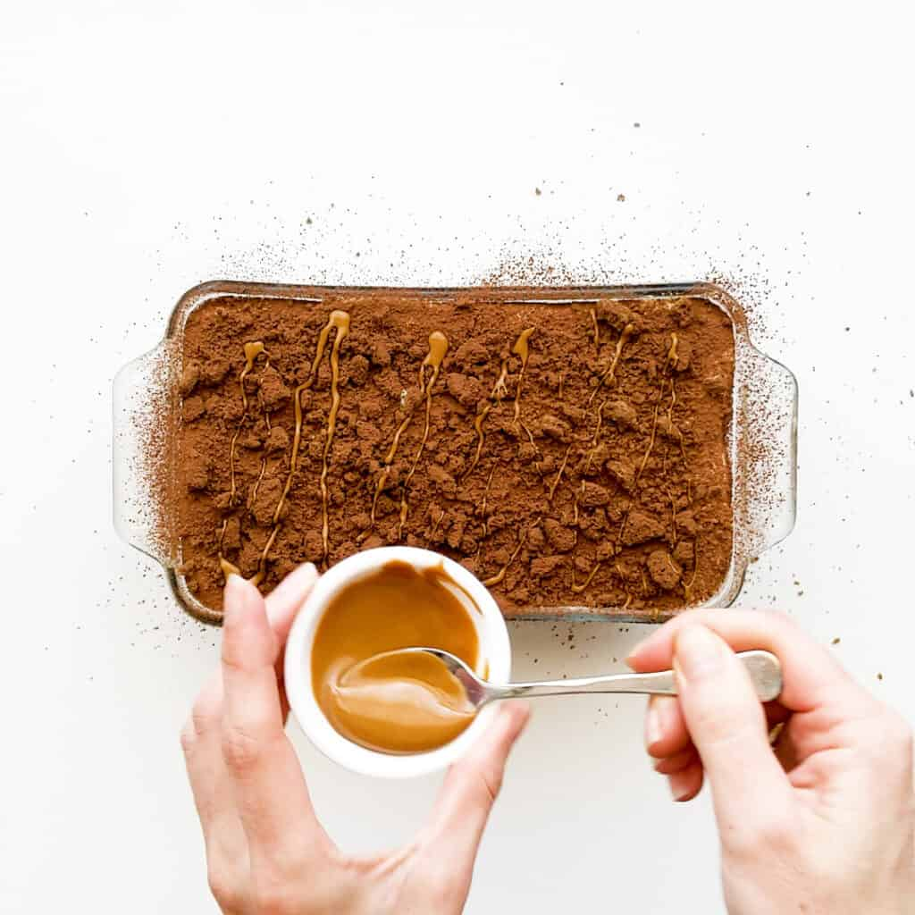 Drizzling speculoos spread on top of tiramisu.