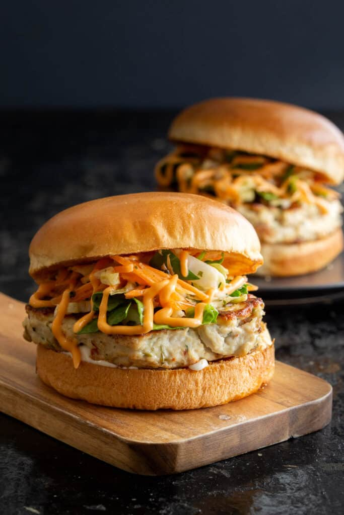 Two Thai chicken burgers on a wooden board and plate.