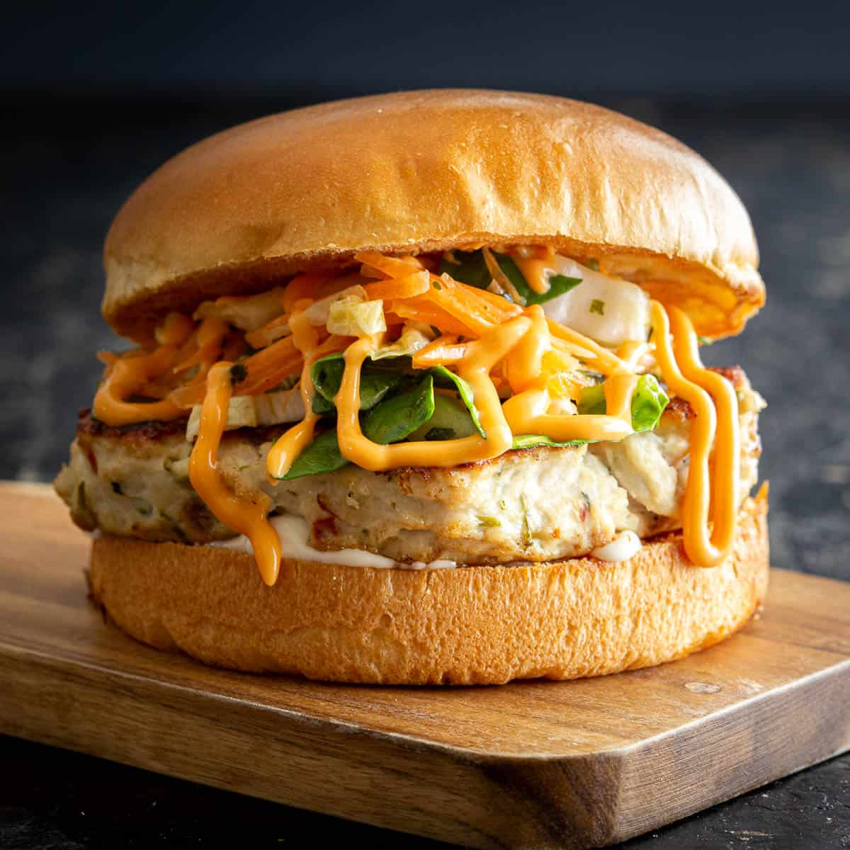A high stacked Thai chicken burger on wooden board.