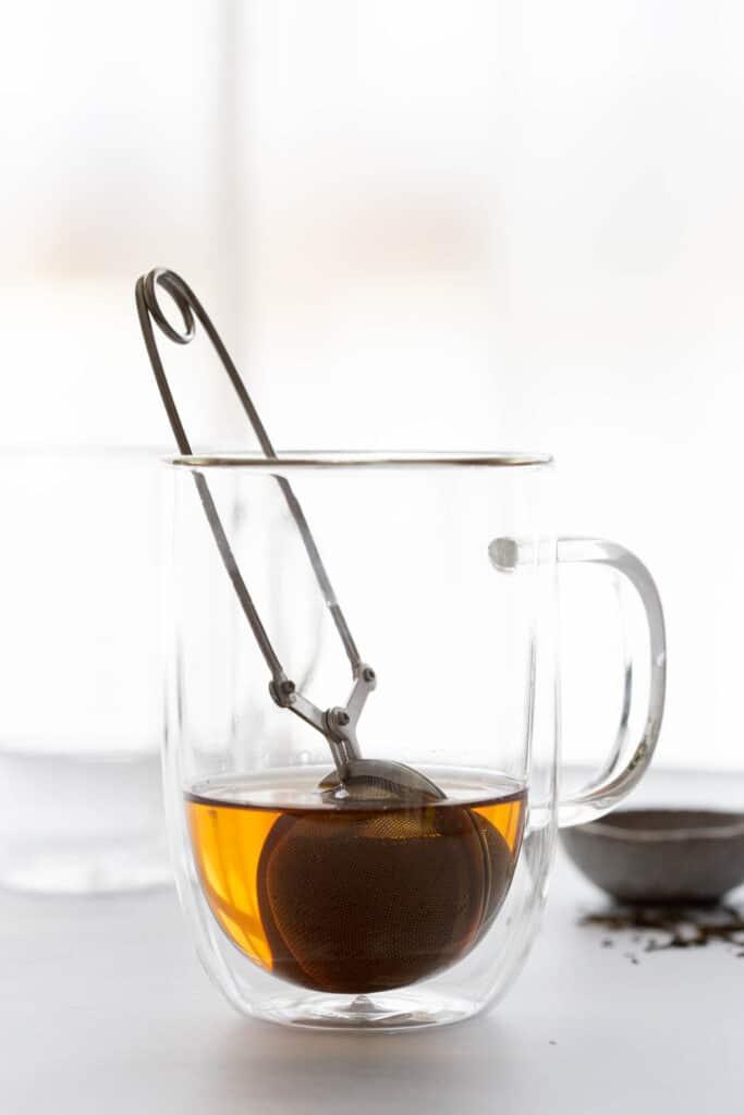 Hojicha tea steeping in a double walled glass.