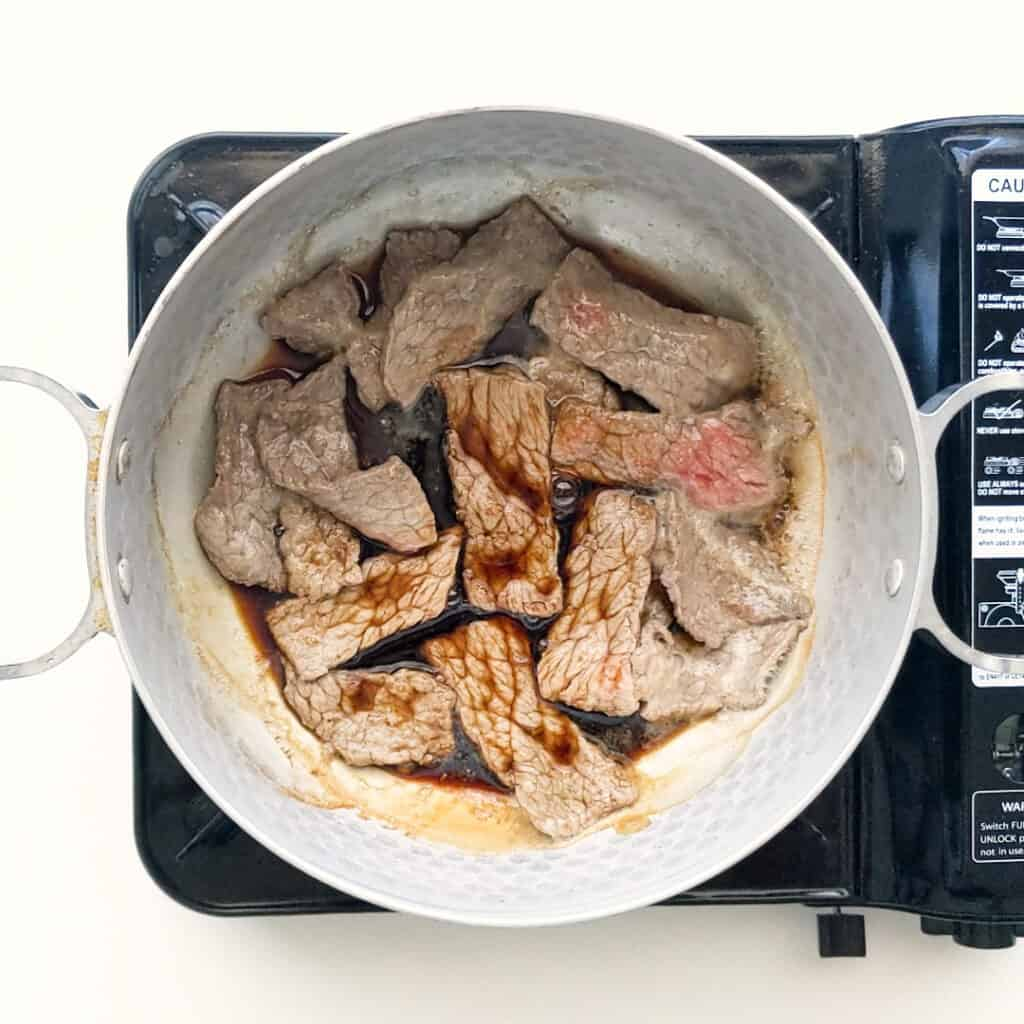 Frying the beef with the soy sauce.