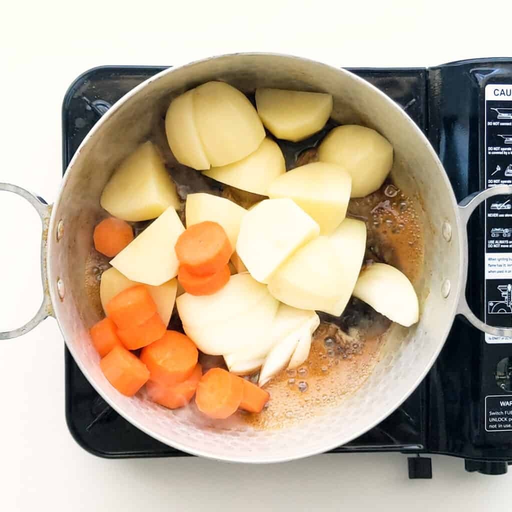 Adding potatoes, carrot and onions to the beef.
