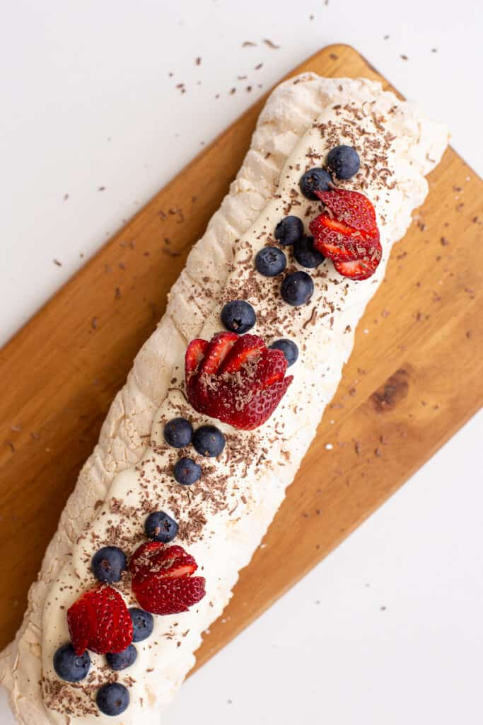 Meringue roulade laid out on a long wooden board.