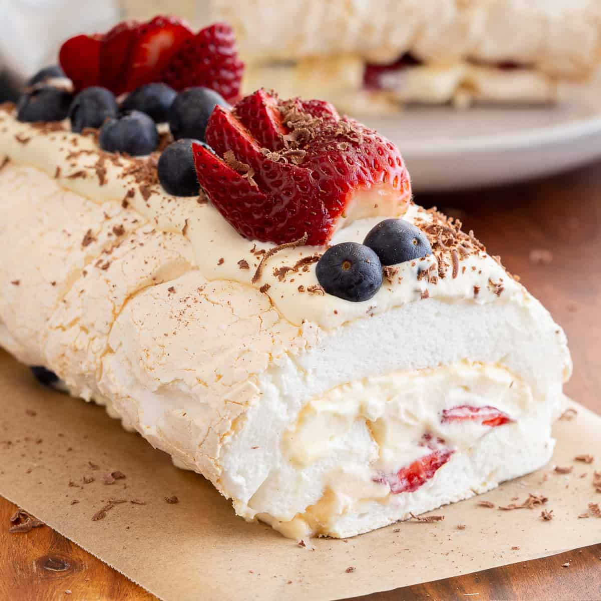 Pavlova roll with berries on a wooden board.