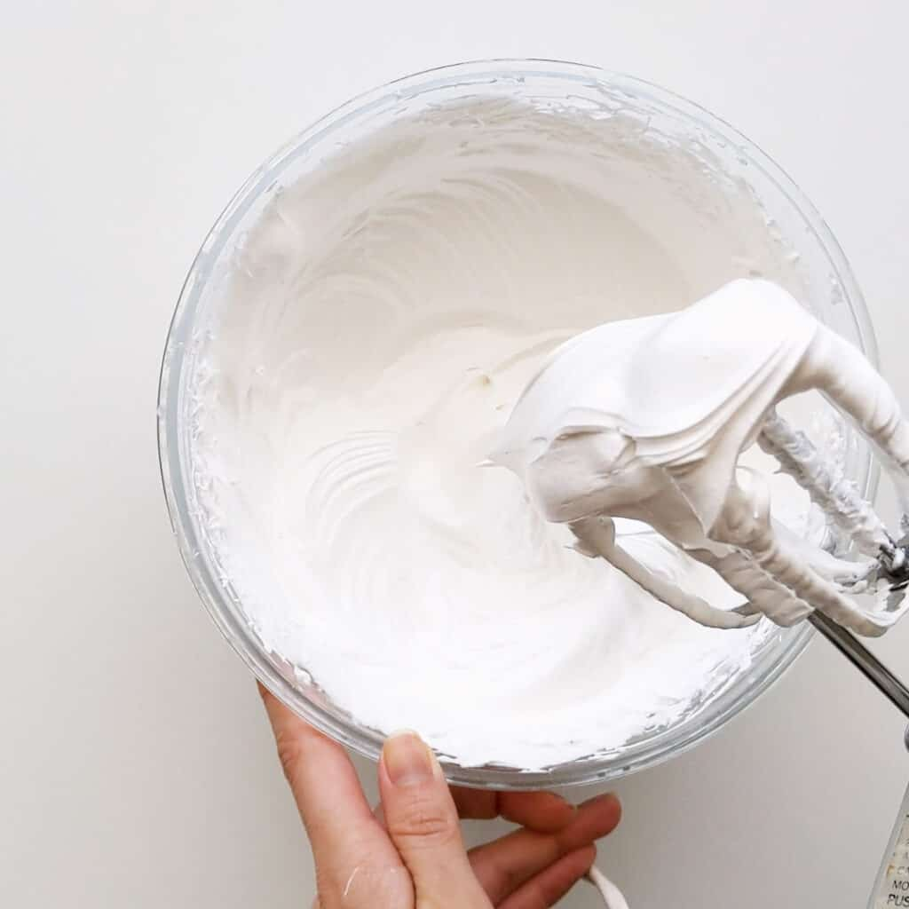 Beating the egg whites until stiff for the meringue.