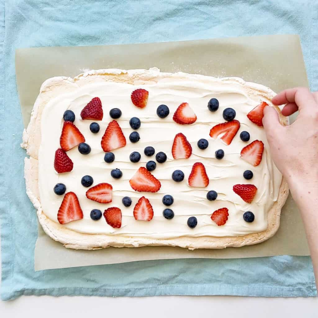 Placing fruit on the pavlova, ready to roll up.