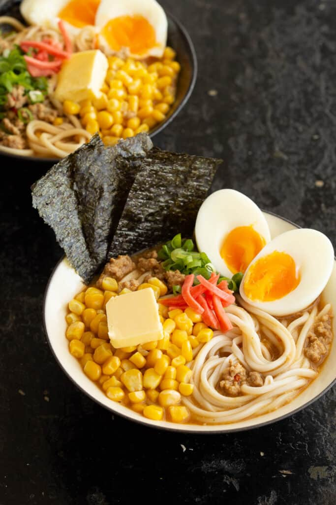 Two bowls of spicy miso ramen full of popular toppings like buttered corn.