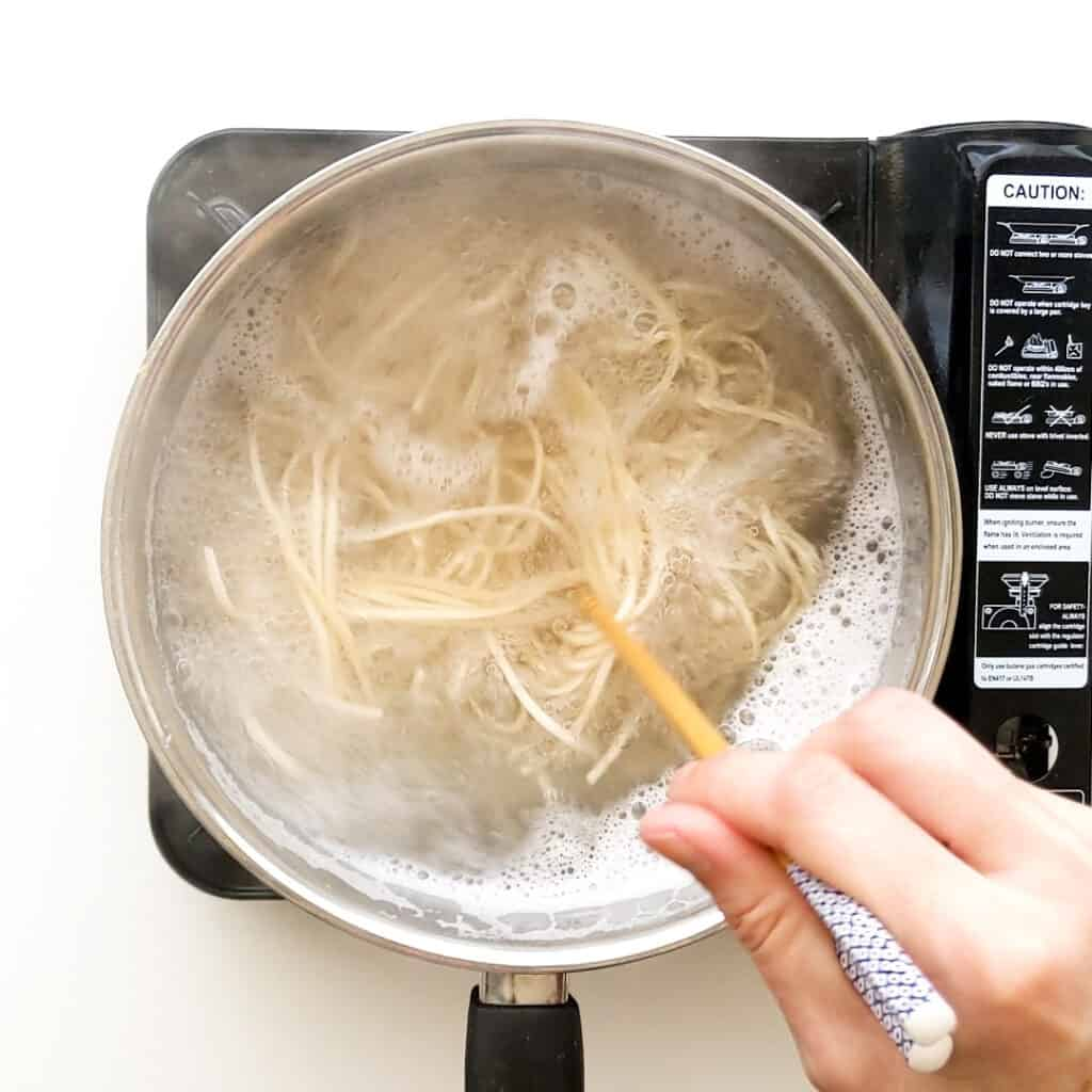 Cooking ramen noodles in boiling water.