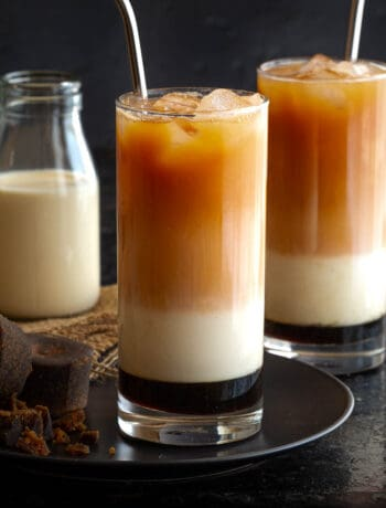 Two glasses of three layer tea and a small bottle of evaporated milk.