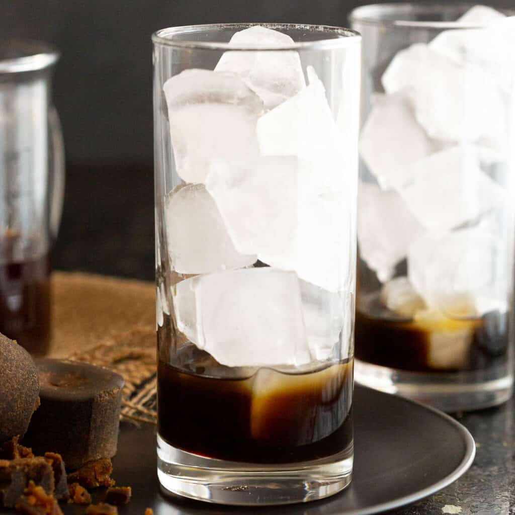 Palm sugar syrup and ice in a tall glass.