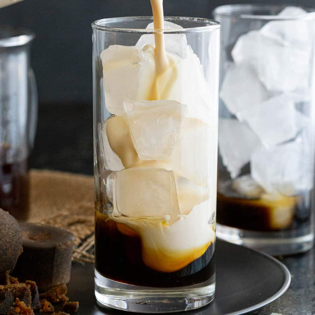 Evaporated milk being poured over ice and gula melaka syrup.