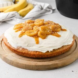 Banana bread cake decorated with cream cheese frosting and caramelised banana