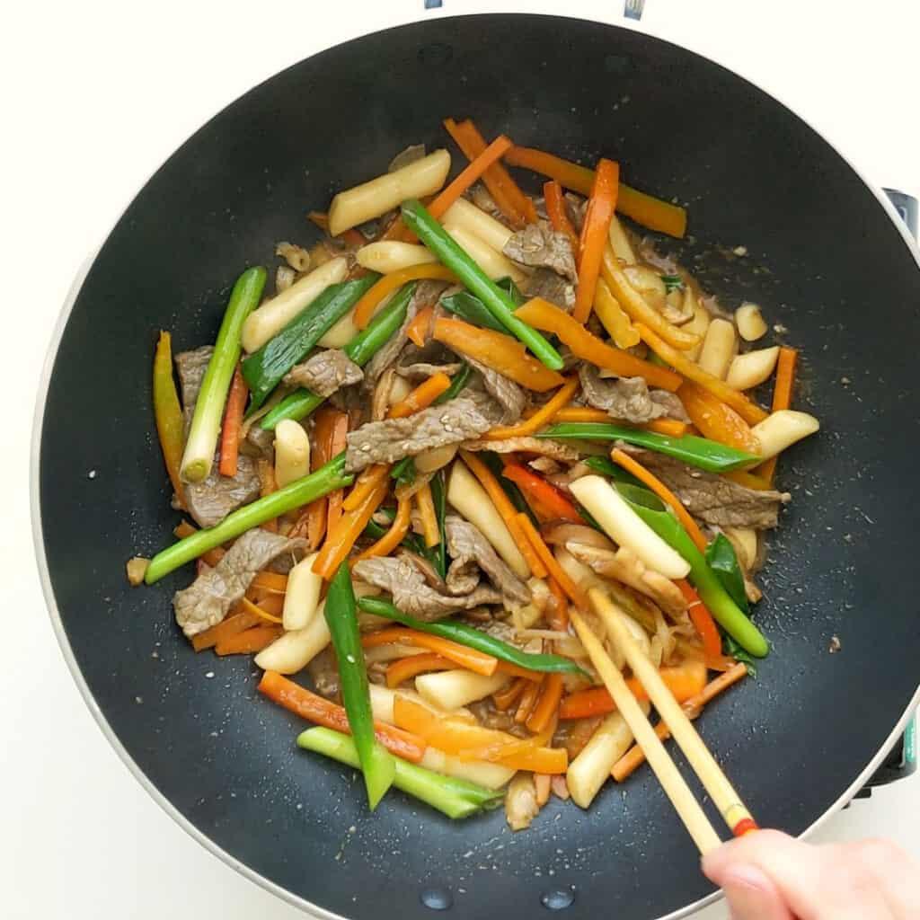Adding spring onion, capsicum and mushroom to the wok.
