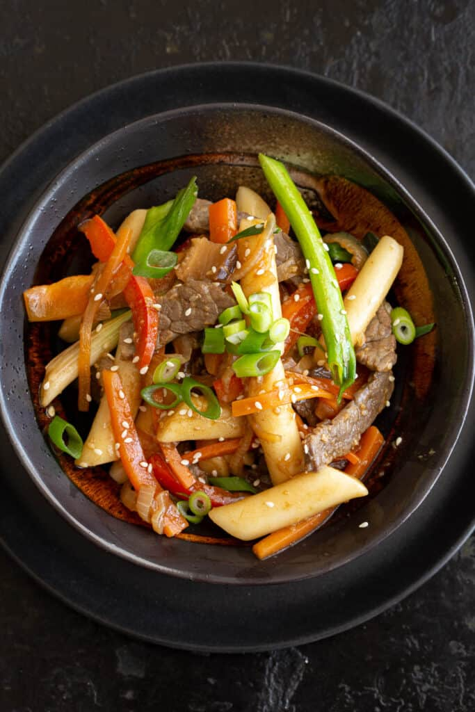 Bowl filled with rice cakes, beef, carrot, capsicum and spring onion.