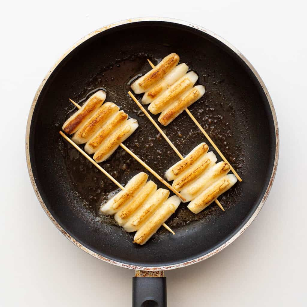 Frying the rice cake skewers.